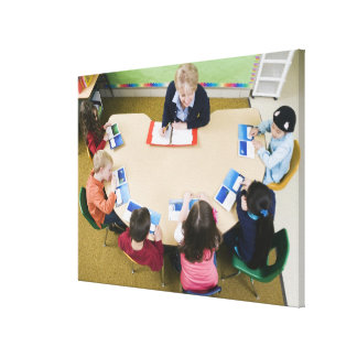 Kindergarten students sitting at table with canvas print