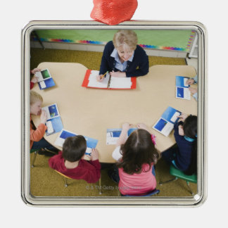 Kindergarten students sitting at table with christmas ornament
