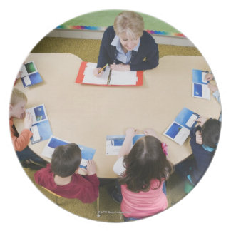 Kindergarten students sitting at table with plate