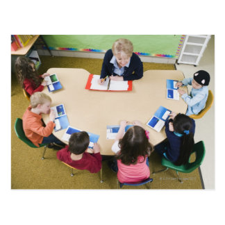 Kindergarten students sitting at table with postcard