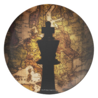 King chess piece on old world map dinner plates