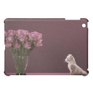 Kitten looking at vase of roses iPad mini case