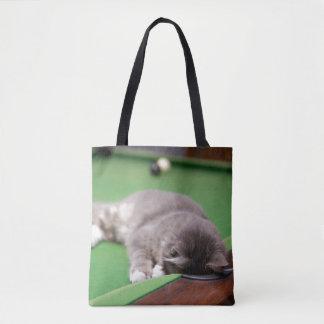Kitten playing on pool table. tote bag