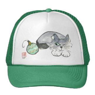 Kitty Eyes a Green and Gold Ornament Cap