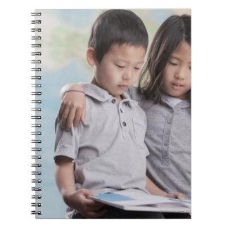 Korean children reading book near map