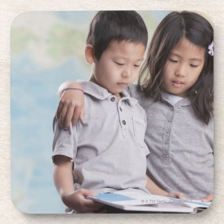 Korean children reading book near map beverage coaster