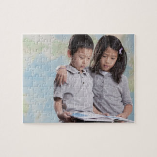 Korean children reading book near map jigsaw puzzle