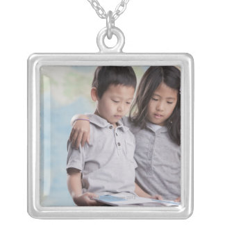 Korean children reading book near map silver plated necklace