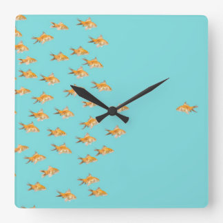 Large group of goldfish facing one lone goldfish square wall clock