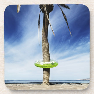 Large palm tree on a sandy beach with inflatable coaster