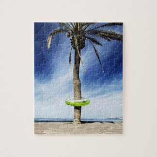 Large palm tree on a sandy beach with inflatable jigsaw puzzle