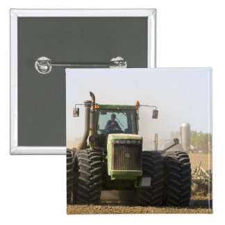 Large tractor cultivating spring soil on a 15 cm square badge