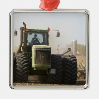 Large tractor cultivating spring soil on a christmas ornament