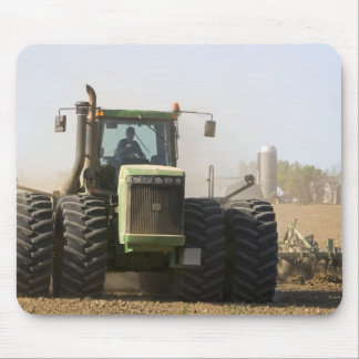 Large tractor cultivating spring soil on a mouse mat