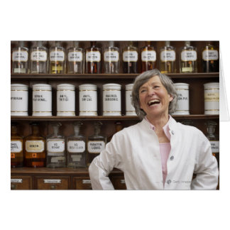 Laughing pharmacist standing in front of a shelf card