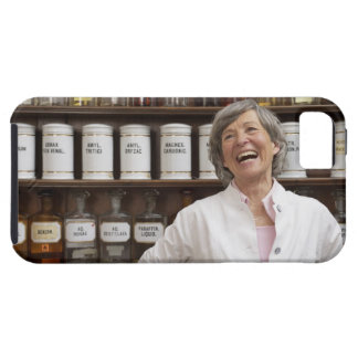 Laughing pharmacist standing in front of a shelf case for the iPhone 5