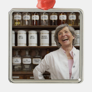 Laughing pharmacist standing in front of a shelf christmas ornament