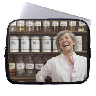 Laughing pharmacist standing in front of a shelf laptop sleeve