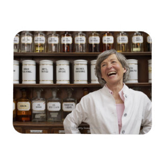 Laughing pharmacist standing in front of a shelf magnet