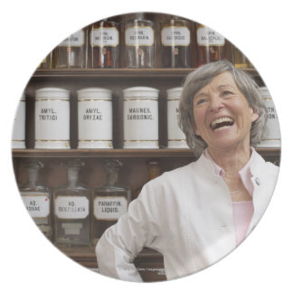 Laughing pharmacist standing in front of a shelf plate