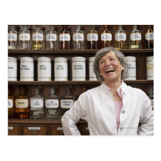 Laughing pharmacist standing in front of a shelf postcard