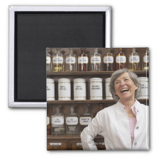 Laughing pharmacist standing in front of a shelf square magnet
