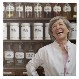 Laughing pharmacist standing in front of a shelf tile