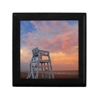 Lifeguard chair with dramatic sky. small square gift box