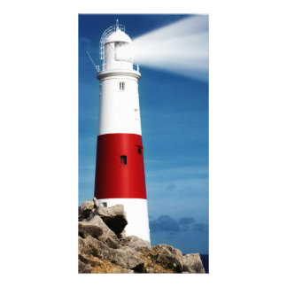Lighthouse on rocks with light beams photo card