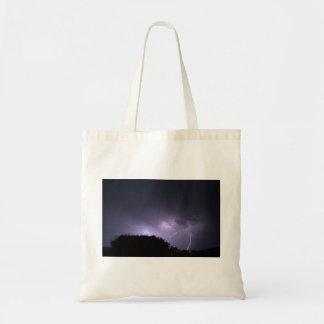 Lightning storm on purple sky tote bags
