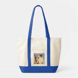 Lioness against blue sky impulse tote bag