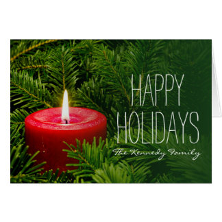 Lit red candle on a bed of evergreen branches card