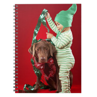 Little boy decorating a dog notebook