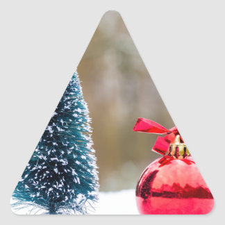 Little christmas tree with red bauble in snow triangle sticker