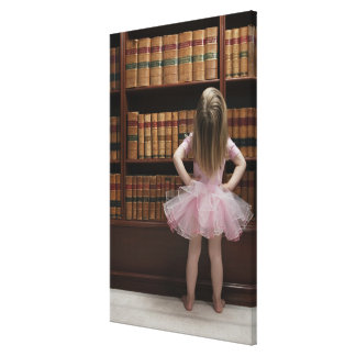 little girl in tutu reading book covers in canvas print