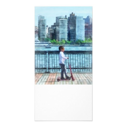 Little Girl on Scooter by Manhattan Skyline Photo Card