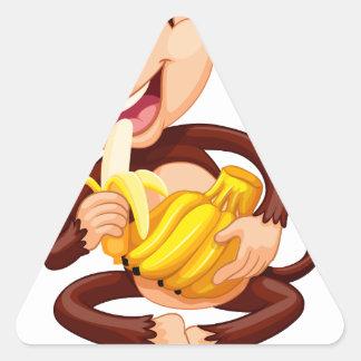 Little monkey eating banana triangle sticker