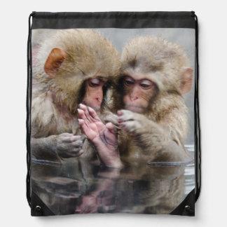 Little monkeys in hot spring, Japan. Backpacks