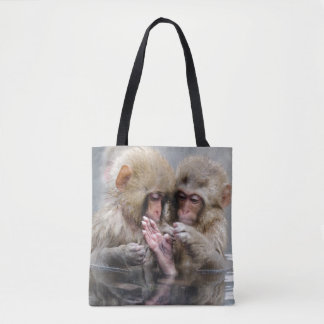 Little monkeys in hot spring, Japan. Tote Bag
