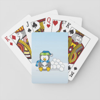 Little penguin sitting with snowballs playing cards