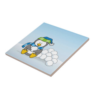 Little penguin sitting with snowballs small square tile