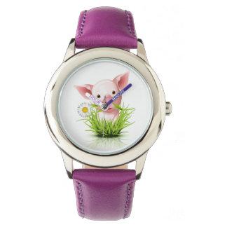 Little pink pig in green grass watch