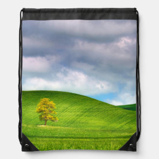 Lone tree surrounded by rolling hills of wheat drawstring bag