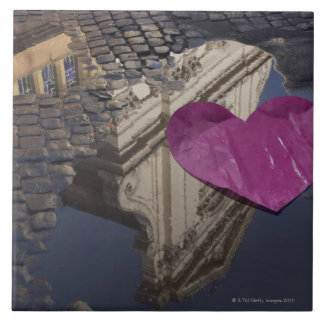 Lonely paper heart floating in a puddle. large square tile
