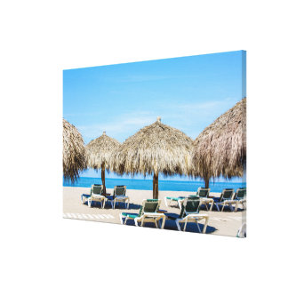 Lounge Chairs And Thatch Umbrellas On Beach Canvas Print
