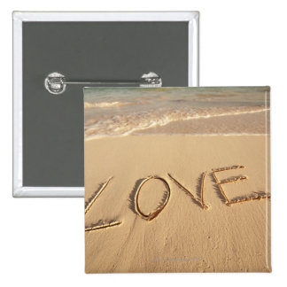 'Love' sand written on the beach with incoming Pinback Buttons