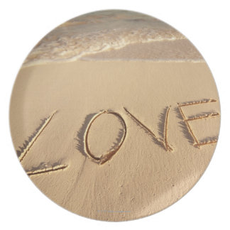 'Love' sand written on the beach with incoming Plates