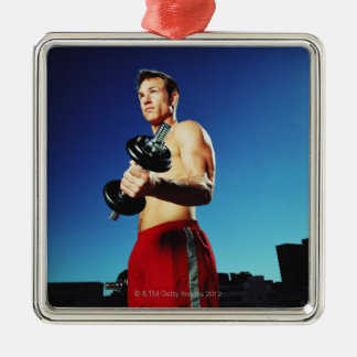 low angle of a man in shorts working out with a christmas ornament
