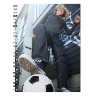 low angle portrait of blond boy with football notebooks