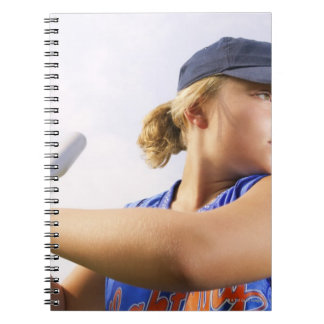 Low angle side view of a softball player looking spiral notebook
